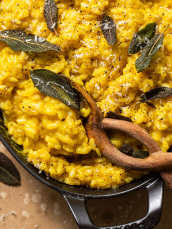 brown serving spoon scooping butternut squash risotto in black gratin dish